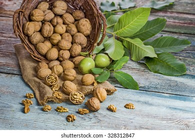 Walnuts with green leaves in garden on the wooden table, on the background wicker basket.