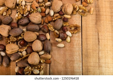 Walnuts, hazelnuts, almonds and pistachios on wooden boards