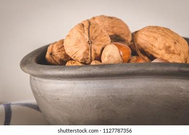 Walnuts, hazelnuts, peanuts and nuts on wooden table.