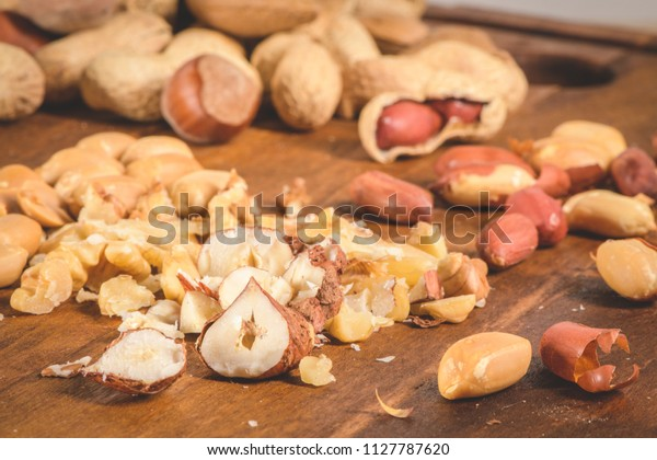 Walnuts, hazelnuts, peanuts and nuts on wooden table.