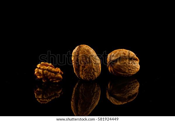 walnuts isolated on black reflective background