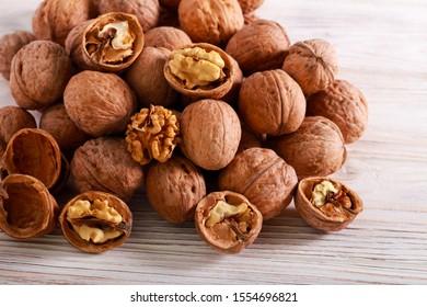 Walnuts in nut shell over light wooden background - Shutterstock ID 1554696821
