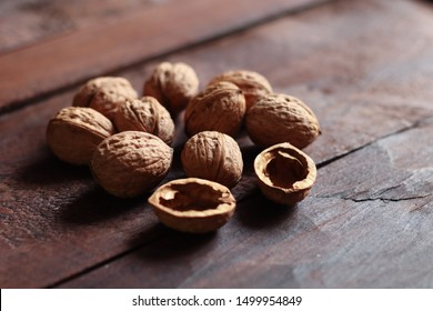 Walnuts and nutshell isolated on the old wooden background in backlight