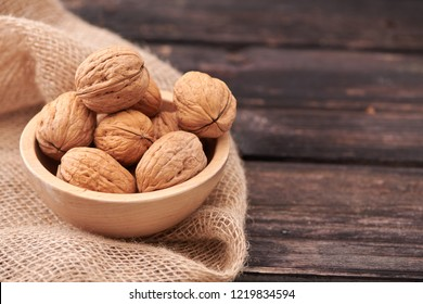 Walnuts on dark vintage table, Walnuts kernels in wooden bowl. Walnut healthy food