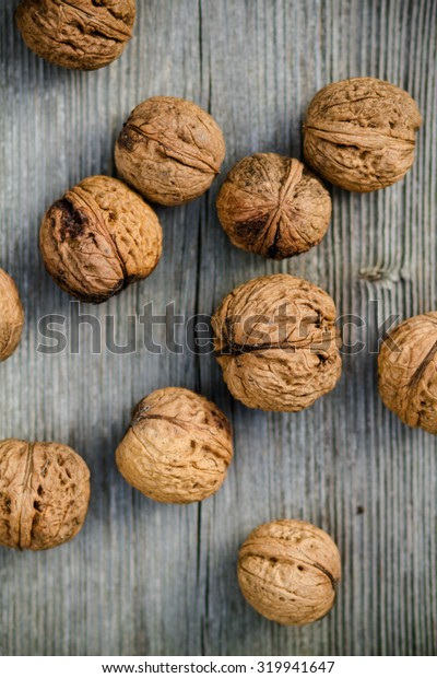 walnuts on old wooden background - top view