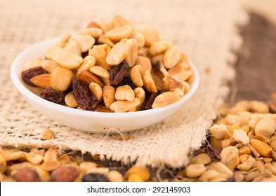 Walnuts and other nuts in a white bowl with raisins