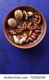 Walnuts and peanuts on a brown clay plate on a blue background