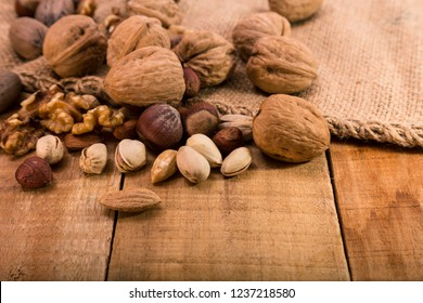 Walnuts, pistachios, hazelnuts, peanuts and almonds are scattered on sackcloth