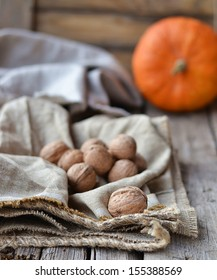walnuts and pumpkin on rustic background