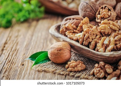Walnuts in wooden bowl. Whole walnut on wood table with green leaves