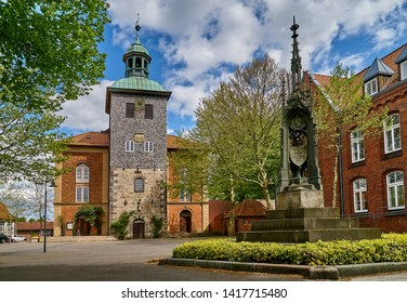 """Walsrode, Germany - May 07, 2019: frontal view of the church """"Stadtkirche"""" together with a memorial in front of it on a sunny spring day with vivid blue sky and white clouds"""