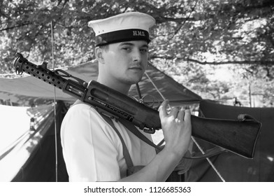 Waltham Gunpowder Mills UK 2018. A reenactor of the RNBCR wears the period uniform of a Royal Navy Sailor of WW2 he stands holding a Lanchester Sub Machine gun at a re-enactment event.
