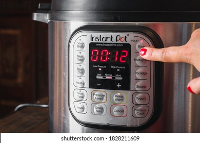 Walvis Bav / Namibia - 10/06/2020: Clicking one of instant pot buttons while cooking in the kitchen