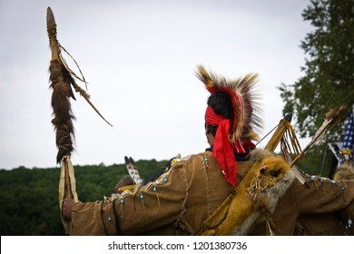 Wampanoag circle dancer wearing traditional deerskin fringed shirt, porcupine roach and a spear as manifestations of his heritage and ethnic identity.