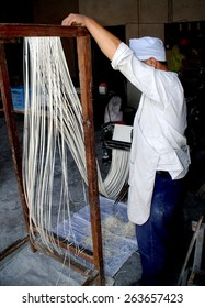 Wan Jia, China - June 11, 2008:  Man making noodles in his shop stretches strings of fresh sliced dough on a special wooden rack