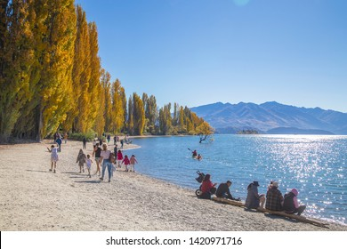 WANAKA LAKE/ NEW ZEALAND - APRIL 17, 2019:  Many Tourists enjoy beautiful view of Wanaka Lake and the lone tree against autumn forrest, mountain and blue sky