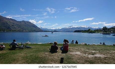 WANAKA, NEW ZEALAND - CIRCA November 2017: Tourist and locals relaxing at Lake Wanaka during an unusually warm spring day.