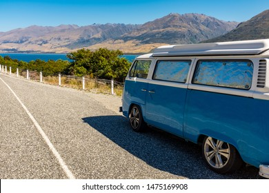 Wanaka, New Zealand, March, 10, 2015; A vintage blue and white campervan parked near a beautiful lake, with mountains in the distance against a clear blue sky, nobody in the image