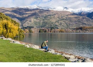 Wanaka New Zealand - May 16th 2015: Man reading paper sitting on rocks at edge of Lake Wanaka