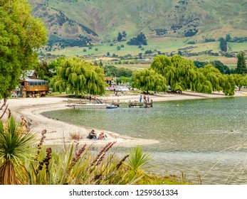WANAKA, NEW ZEALAND/DECEMBER 11, 2018: A young couple relax together on a sandy beach of Lake Wanaka early in summer in the resort town of Wanaka on the South Island of New Zealand.