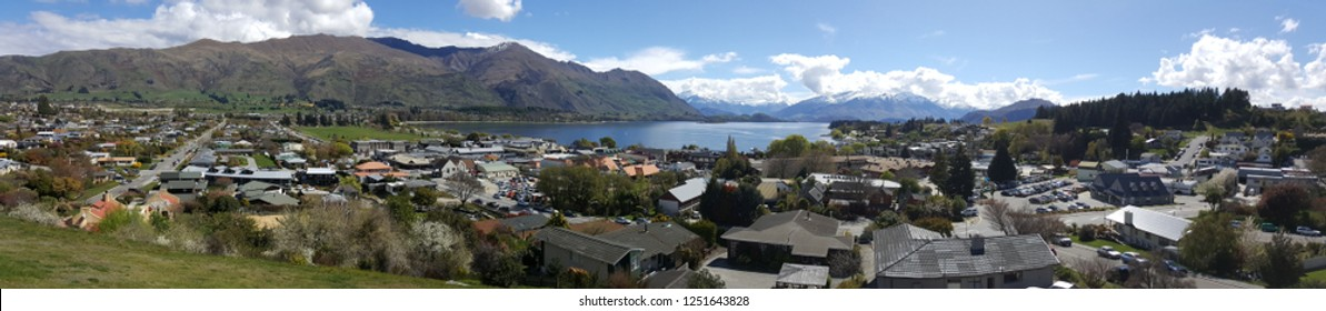Wanaka is a resort town on New Zealand. This photo was taken on top of Elephant Hill. The view overlooks the entire tourist town of Wanaka. The image has blue sky and mountain.