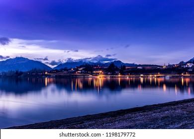 Wanaka Yacht Club lights reflected on calm water of Lake Wanaka at sunset