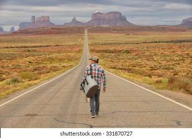 Wanderer or loner in Monument Valley walking down an empty road