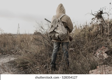 wandering boy. boy with a gun. boy goes to an abandoned building. Post apocalypse.  traveling on foot in a post-apocalyptic world in search of food. boy standing in a field