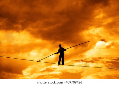 Wandering tightrope walker playing on yellow sky background. Silhouette of Equilibrist businessman with pole on the rope