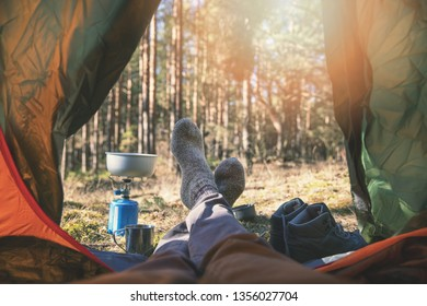 wanderlust outdoor camping - traveler feet out of the tent