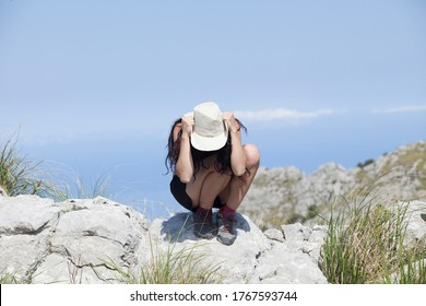 Wanderlust of a sporty and young woman The woman is on top of a mountain overlooking the peaks of the tramuntana in Majorca, The woman is wearing  trekking clothes, a hat and a sunglasses. Summer Vaca