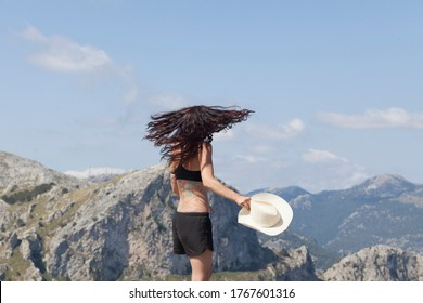 Wanderlust of a sporty and young woman The woman is on top of a mountain overlooking the peaks of the tramuntana in Majorca, The woman is wearing black trekking clothes, a hat and glasses. Summer Vaca
