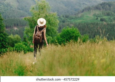 wanderlust. stylish hipster woman with backpack looking at  amazing woods and mountains in summer, travel concept, space for text