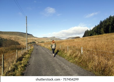 Wanderlust and travel concept. Attractive young woman hiking on a on a country lane towards Pen y Fan mountain with a rugged landscape and blue sky.
