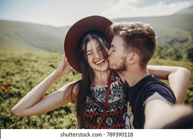 wanderlust and travel together concept. stylish couple travelers in hat making selfie at mountains. hipster family smiling and kissing on top of mountain. space for text. atmospheric moment