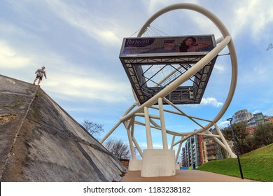 WANDSWORTH, LONDON - January 2, 2018: young man is standing on small architectural forms on the street. Sport parkour. Wandsworth Roundabout sculpture. Billboard, hoarding is large outdoor advertising