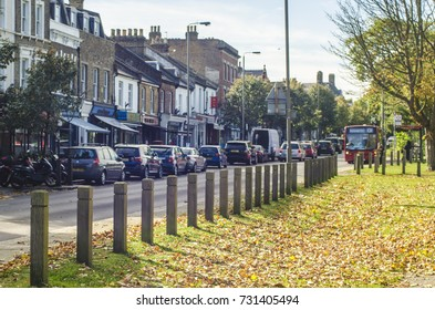 WANDSWORTH, LONDON: OCTOBER, 2017: Bellevue Road on Wandsworth Common in south west London. A high street with coffee, fashion and food shops next to grassy field and woodland space.