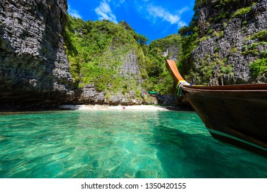 Wang Long Bay with crystal turquoise water, Tropical island Koh Phi Phi Don, Krabi Province, Thailand - Long boat in beautiful lagoon with rocks covered with a plants