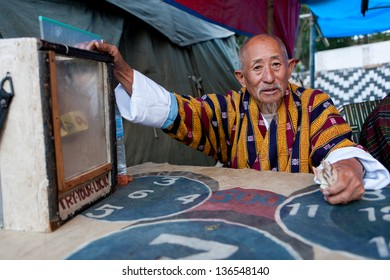WANGDI,BHUTAN - SEPTEMBER 24:Buthanese man invites people for a game of dice at the Wangdi Festival on September 24,2012 in Wangdi,Bhutan.Gambling is a very popular activity in Bhutan.