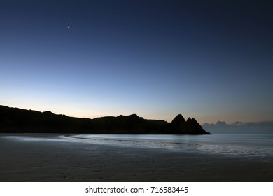 A waning crescent moon and a blue dawn at Three Cliffs Bay on the Gower peninsula in Swansea, South Wales, UK
