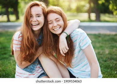Wanna hug her forever. Portrait of happy and carefree two twin sisters with natural red hair and freckles, laughing out loud and cuddling, fooling around while resting in park on fresh green grass.