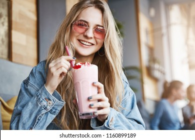 Wanna share cocktail with me. Joyful and carefree friendly-looking caucasian woman in trendy pink sunglasses, holding pink and tasty drink, smiling happily while having funny conversation