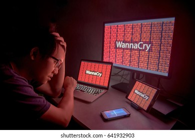 WannaCry ransomware attack on desktop screen, notebook and smartphone, internet cyber attack with Anonymous calling on smart phone to get the ransoms payment to decrypt the code