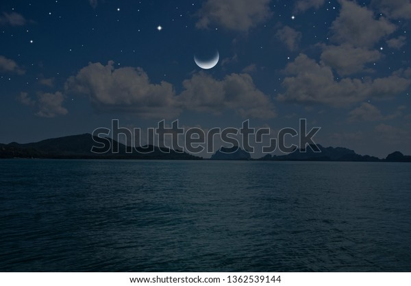 Wanning moon and bright stars over blue sea