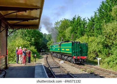 WANSFORD, CAMBRIDGESHIRE, UK - CIRCA AUGUST 2017: Train station view of a British steam locomotive seen underway of section of track. In view is a period railway station with people watching.
