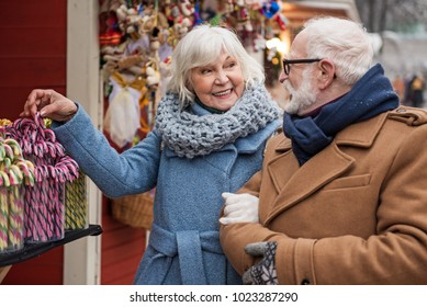 I want to buy this candy. Joyful senior woman is choosing holiday lollipop and smiling. Man is looking at her with happiness