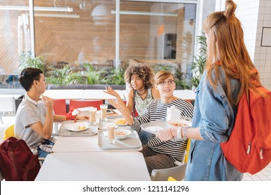 Want to eat. Handsome blonde boy keeping smile on his face while welcoming pretty girl in canteen