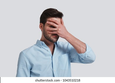 I want to know everything.  Handsome young man covering eyes with hand and peeking while standing grey background
