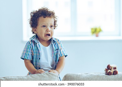 I want to play! Little African baby boy crying and looking away while standing on the couch at home