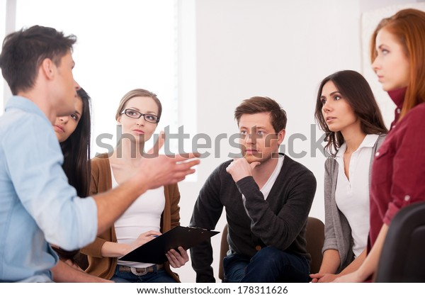 I want to share my problem. Group of people sitting close to each other while man telling something and gesturing